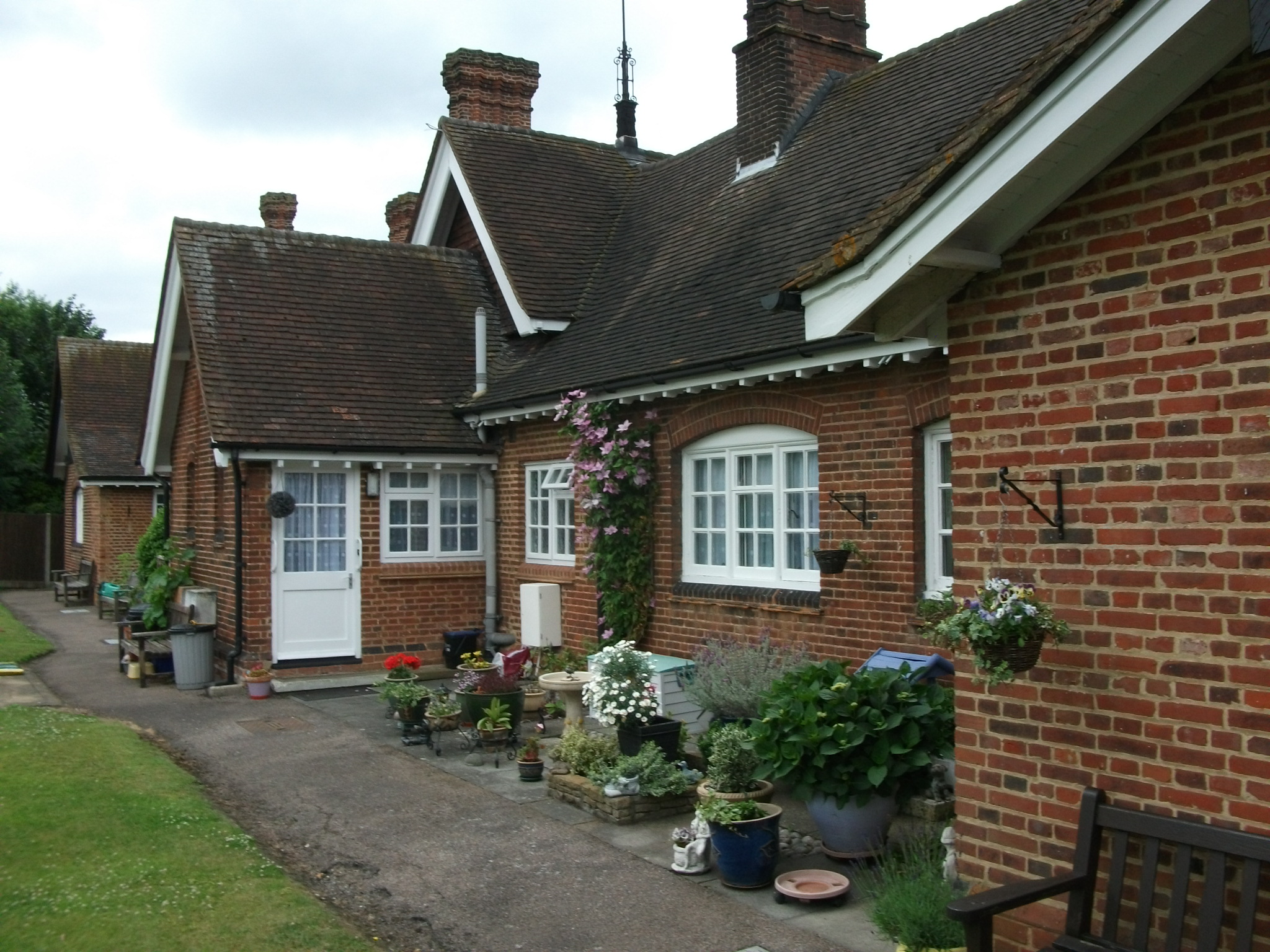 Shen Place Almshouses garden view showing pots and hanging baskets